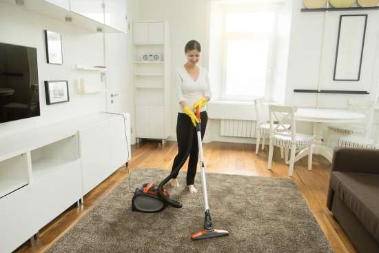 Young smiling woman vacuum cleaning the carpet